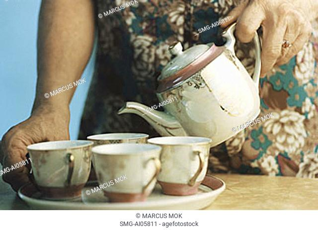 Elderly person pouring tea into cups