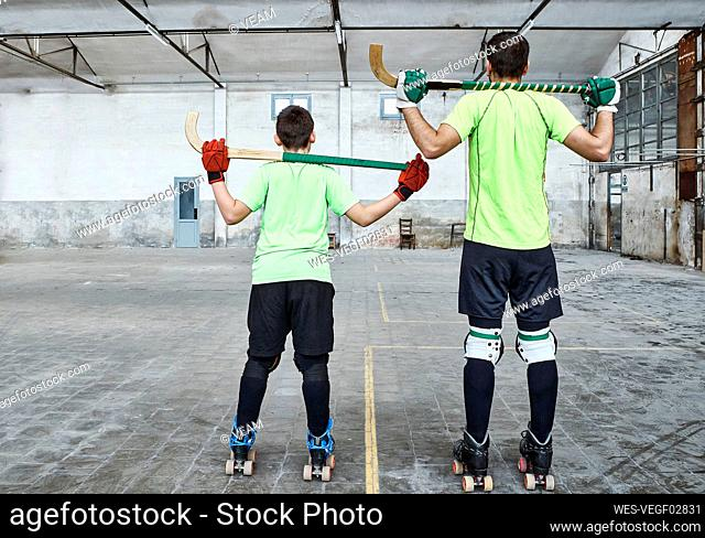 Father and son in sports uniform holding hockey sticks at court