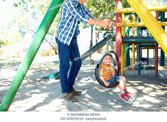 Low section of father pushing son sitting on swing