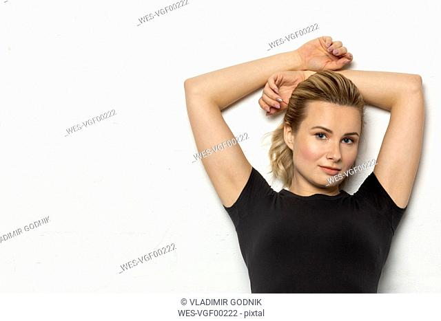 Portrait of blond woman wearing black jersey in front of white background