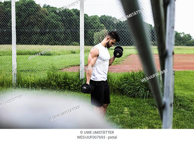 Athlete exercising with dumbbells on sports field