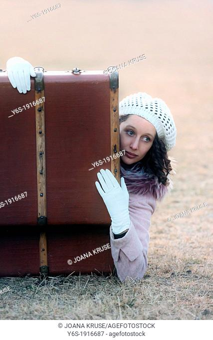 a woman is lying in an old suitcase