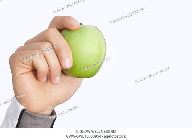 Person's hand holding a green apple