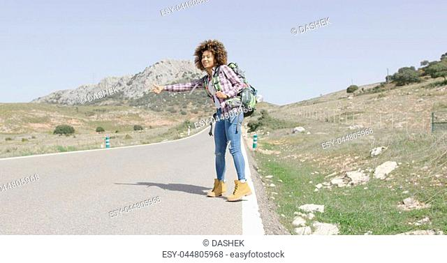 Young woman in casual outfit standing on road with backpack and hitch hiking on of mountains