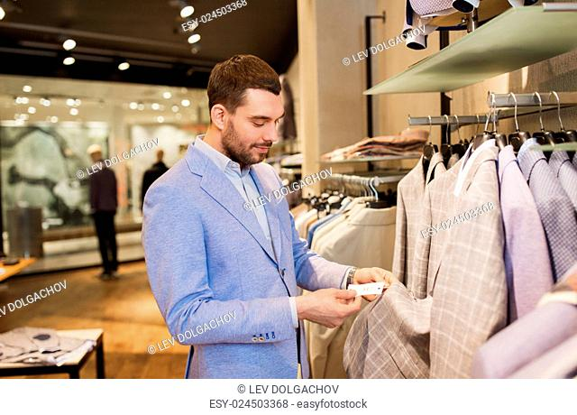 sale, shopping, fashion, style and people concept - elegant young man in jacket choosing clothes and looking at price tag in mall or clothing store