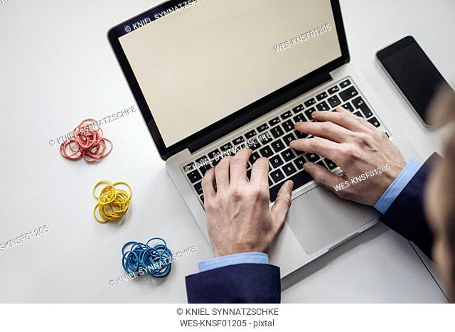Close-up of businessman using smoking laptop next to rubber bands