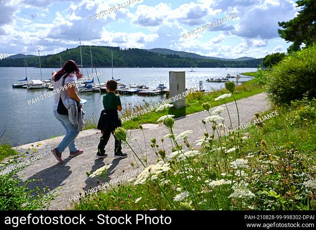 PRODUCTION - 26 August 2021, Hessen, Waldeck: Mother and child stroll along the lakeside promenade of the Edersee near Waldeck in the sunshine