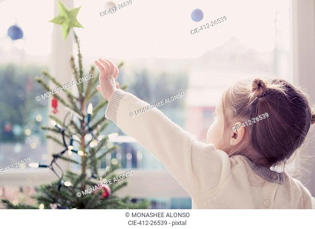 Girl reaching for start on Christmas tree