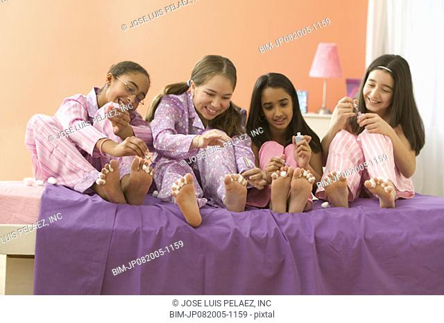 Four girls sitting on bed painting toenails