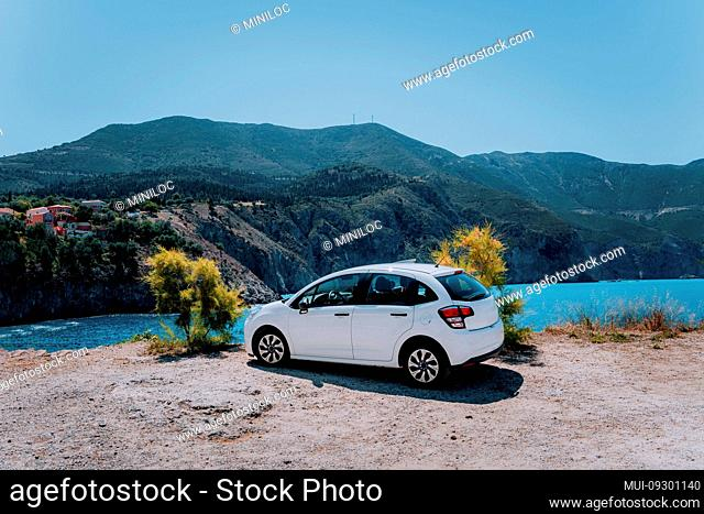 Vacation travel with car concept. Rental hired car in front of amazing bay with turquoise water. Discover Mediterranean Islands