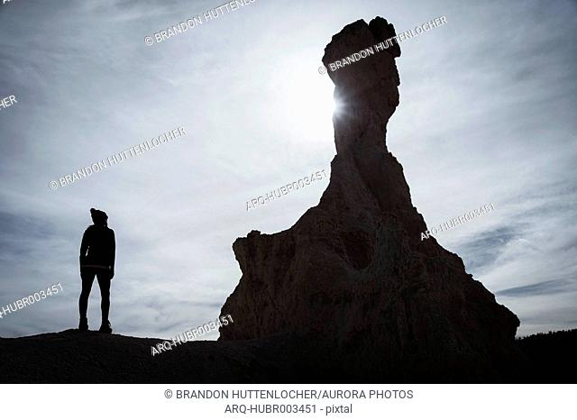 Lone female hiker standing and looking at view of hoodoo in Bryce Canyon National Park, Utah, USA