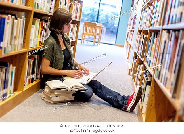 An 18 year old girl sitting on the floor in a library with a laptop computer and books stacked next to her