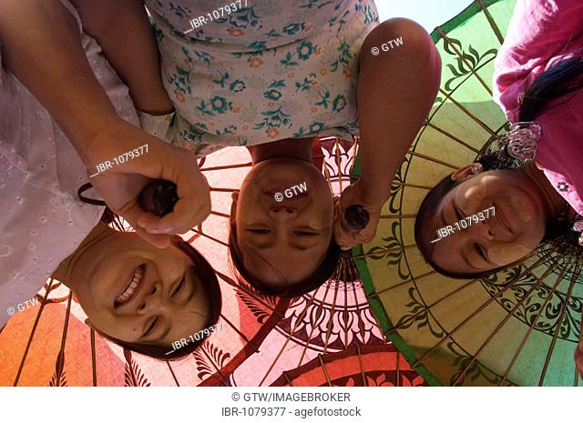 View from below of young Burmese women with coloured parasols, Bagan, Myanmar
