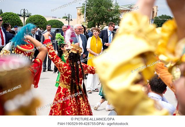 29 May 2019, Uzbekistan, Chiwa: Federal President Frank-Walter Steinmeier and his wife Elke Büdenbender are greeted by singing and dancing children in the old...