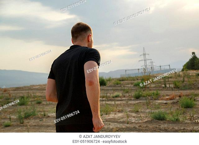 portrait of a young Caucasian guy in a black t-shirt and black shorts running over rough terrain during sunset