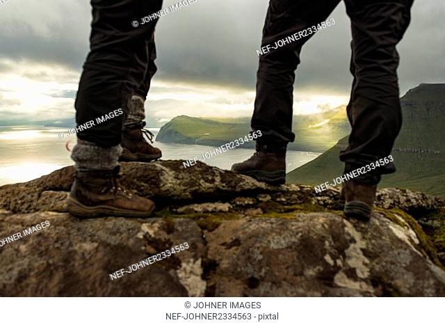 Hikers standing on rocks, low section