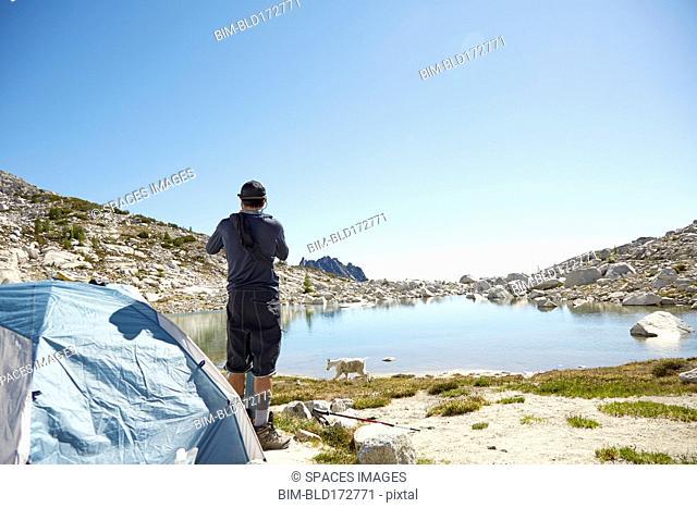 Man standing at tent at campsite near rural lake
