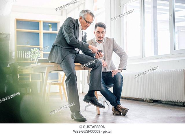 Senior businessman showing cell phone to young businessman