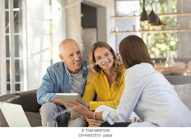 Financial advisor with digital tablet meeting with couple in living room