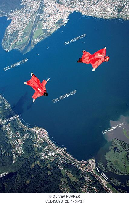 Two wingsuit skydiver pilots team training and flying close together over lake, Locarno, Tessin, Switzerland