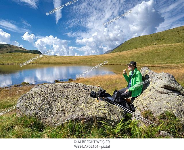 Italy, Lombardy, hiker sitting at lake and eating an apple