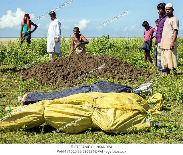 Men bury the bodies of Rohingya women that washed up on a beach near the city of Teknaf, in southern Bangladesh, 10 October 2017