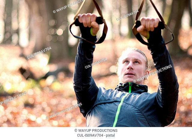 Mid adult man using resistance bands, looking up