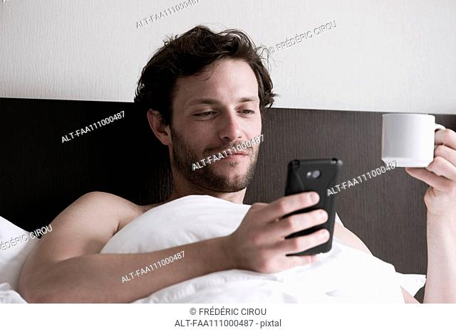 Man in bed using smartphone and drinking hot drink