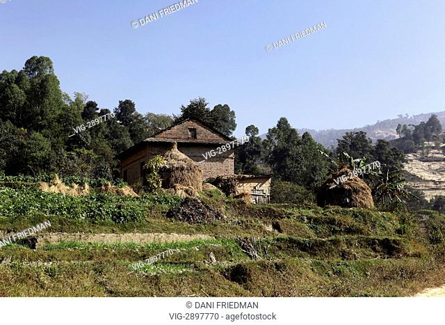 An old traditional mud-brick farmhouse and haystacks in the Sankhu Village in Nepal. The Sankhu Village is located along an ancient trade route from Tibet which...