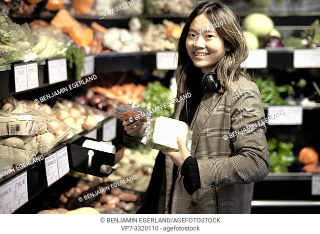 young Asian woman buying shrink-wrapped vegetables in supermarket, welded in plastic foil, in Paris, France