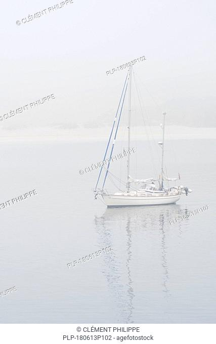 Sailboat / sailing boat / yacht with lowered sails anchored near beach during bad visibility due to thick fog / dense mist