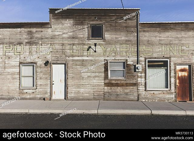 Old wooden building on Main Street, rusted door and boarded up windows