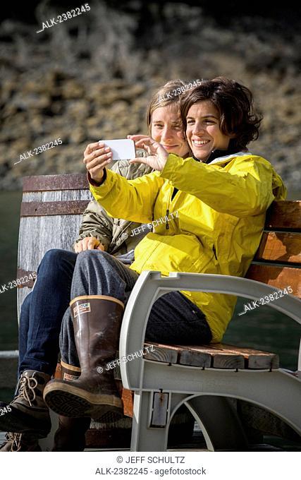 Women take self portrait with smart phone at Tutka Bay Lodge, Alaska, Summer