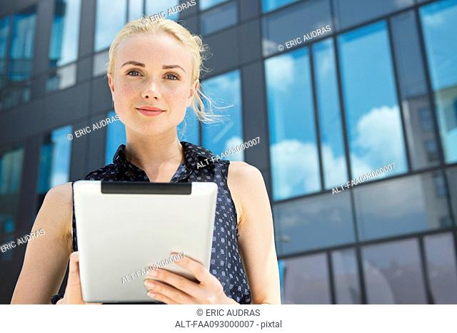 Young businesswoman using digital tablet outdoors