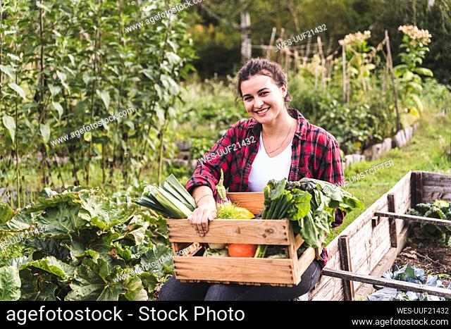 Smiling young woman with vegetables in crate sitting against plants at garden