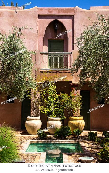 Typical moroccan architecture, riad adobe walls , fountain and flower pots, Morocco