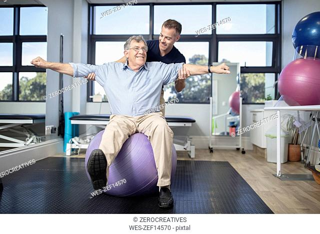 Senior man exercising with fitness ball at physio's practice