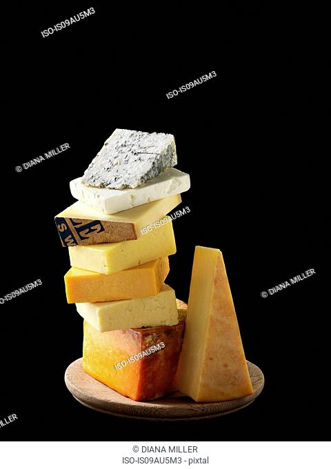 Cheese selection stacked on cheese board with black background