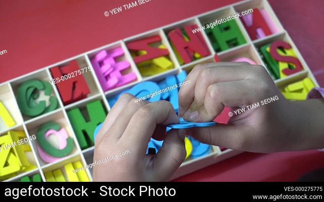 A little girl separate education ABC block. Preschool activity