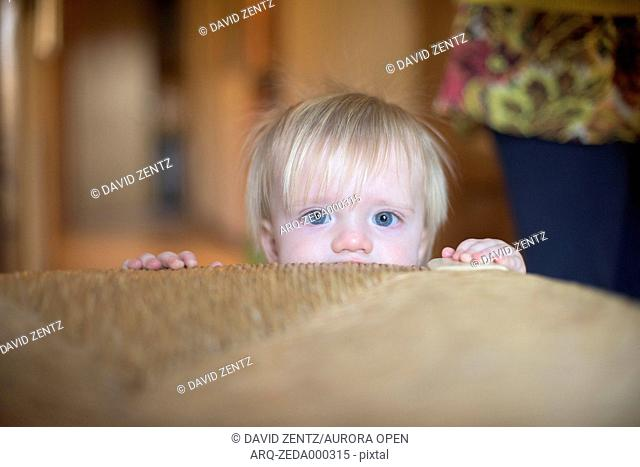 A baby peeks out behind a wicker chair in Emerald Isle, North Carolina, on Dec. 25, 2014