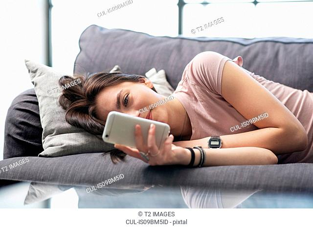 Teenage girl lying on sofa looking at smartphone