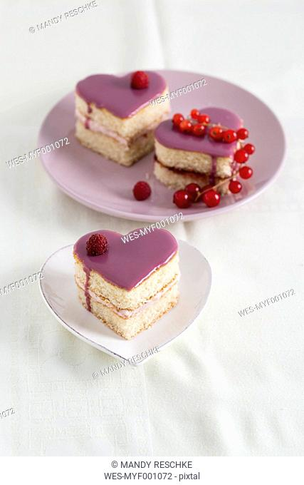 Small biscuit cakes in heart shape with raspberry cream and currant jelly