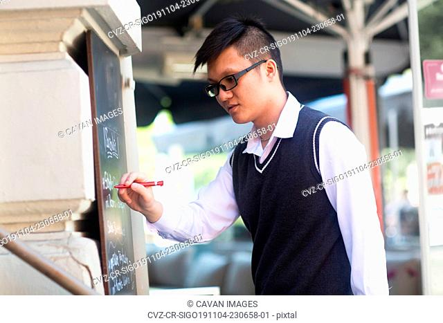 young asia waiter in a bar writing new offers