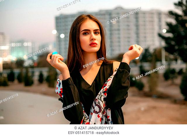 Young beautiful girl in a black jacket with a scarf posing in the evening on the street