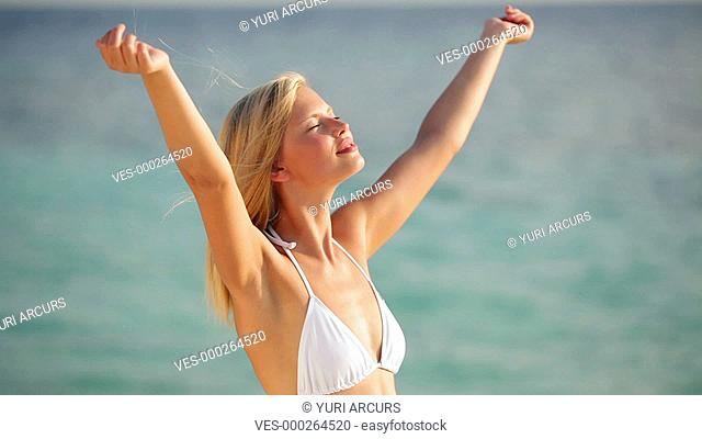 Video of a carefree woman enjoying a sunny day with her arms outstretched at the beach