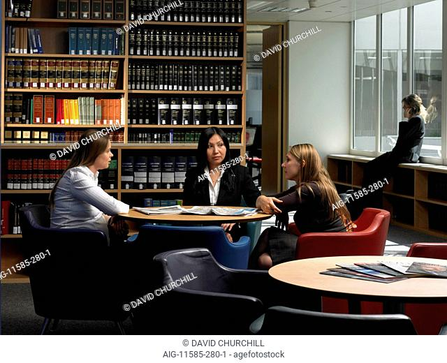 Office life and interiors (model released). Female employees in staff room conversing with one woman talking on mobile phone by window