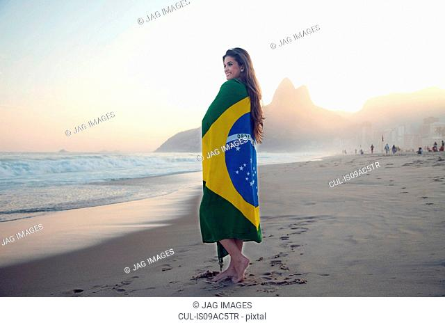 Young woman on beach, wrapped in Brazilian Flag