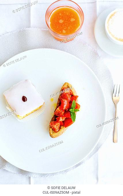 Overhead view of traditional Italian breakfast with tomatoes, sweet cake and cappuccino, Campania, Italy