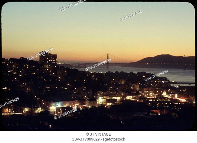 Illuminated Cityscape with Golden Gate Bridge in Background at Sunset, San Francisco, California, USA, 1957