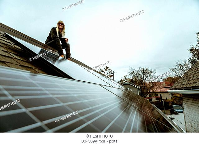 Portrait of mid adult woman sitting on newly solar paneled house roof